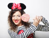 Young curly woman with mouse ears holding lollipop. Young happy curly woman with mouse ears holding lollipop Stock Photo