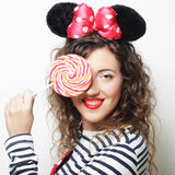 Young curly woman with mouse ears holding lollipop Stock Images