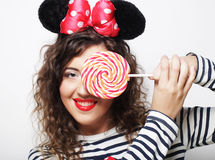 Young curly woman with mouse ears holding lollipop. Young happy curly woman with mouse ears holding lollipop Stock Photos