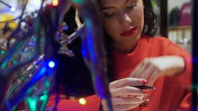 Woman writes her wish list. Young curly woman in a red sweater and red lips writes her wish list for Christmas in her personal diary stock video