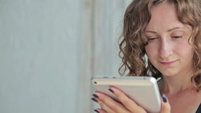 Young curly woman sitting on bed with tablet pc. Dolly shot stock footage