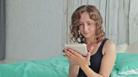 Young curly woman sitting on bed with tablet pc stock video footage