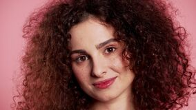 Young curly woman with trendy glitter freckles make-up. Portrait of flirting beautiful girl on pink studio background.