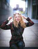 Young curly woman using her phone and relax in the city Royalty Free Stock Images