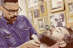 Young customer on a beard shaving session Royalty Free Stock Photo
