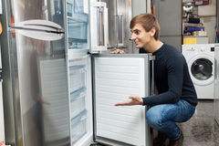 Young customer choosing new refrigerator. In domestic appliances store royalty free stock images