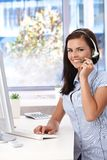 Young customer service operator working smiling. Young customer service operator working in bright office, smiling, looking at camera Royalty Free Stock Image