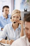 Operator talking on headset. Young customer service operators working in office, smiling stock images
