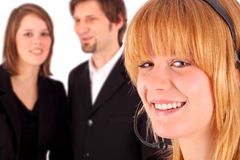 Young customer service representative. With business people in background Royalty Free Stock Images