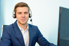 Young Customer Support Phone Operator with Headset at his Working Place in Office. Royalty Free Stock Photos