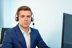 Young Customer Support Phone Operator with Headset at his Working Place in Office. Stock Photography