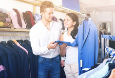 Young customers selecting jacket. Two young customers selecting a jacket in the clothing shop. Focus on both persons Royalty Free Stock Images
