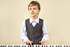 Young cut boy play the keys of digital piano Royalty Free Stock Photography