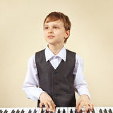 Young cut boy in suit playing the electronic synth Royalty Free Stock Image