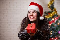 Young cute amused charming woman in Santa cap with funny face an. D a gift box in hand. New Year, Christmas, gift, surprise, celebration, emotions concept Stock Image
