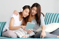 Young cute asia lesbian couple using tablet with happiness at ho. Me, lgbt, homosexual, lesbian couple lifestyle royalty free stock photos