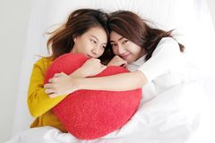 Young cute asia lesbians holding red heart shape willow together. Lying and smiling with happiness on white bed, LGBT, couple lesbians, valentine`s day concept Royalty Free Stock Photos