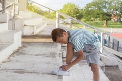 An young cute Asian boy is lacing white shoe rope. In stadium Royalty Free Stock Images