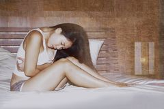 Young cute Asian Chinese woman on her 20s suffering period pain holding her stomach or belly feeling unwell in painful face expres. Sion lying on bed at home in Royalty Free Stock Images
