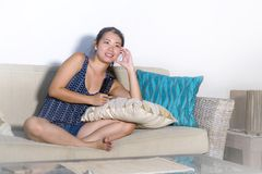 Young cute Asian Chinese woman smiling happy sitting at home sofa couch watching TV show or television comedy movie holding remote. Enjoying relaxed having fun Stock Image