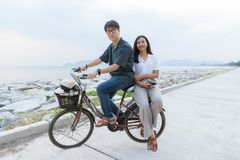The young cute Asian couple are sitting on a bicycle together. With casual clothes. They are in a relationship, looks happy, enjoy and relax, has a beautiful royalty free stock photos