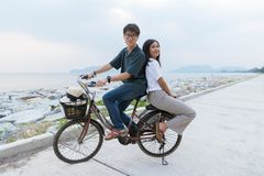 The young cute Asian couple are sitting on a bicycle together. With casual clothes. They are smilng and feels happy, enjoy and relax. They are in a relationship royalty free stock photography