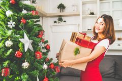 Young cute Asian girl holding X`Mas present boxes, Christmas tree decorated with ornament at home living room royalty free stock photo