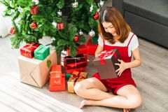 Young cute Asian girl holding red X`Mas present box, Christmas tree decorated with ornament at home living room. Xmas celebration event preparation, or winter stock photo