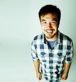 Young cute asian man on white background gesturing emotional, po Stock Images