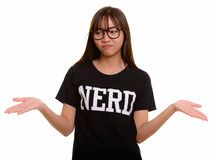 Young cute Asian nerd teenage girl shrugging shoulders. Isolated against white background stock image
