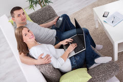 Young cute attractive couple internet shopping Stock Images