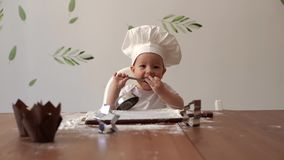 Cute baby in a chef`s cap smiles at the table and licks the flour from a spoon stock video