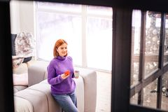 Young cute beaming girl in a violet sweater looking thoughtful stock photography
