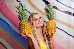 Young, cute, beautiful slim blonde woman with african braids and with  pineapples in her hands Stock Images