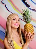 Young, cute, beautiful slim blonde woman with african braids and with  pineapples in her hands Royalty Free Stock Photo
