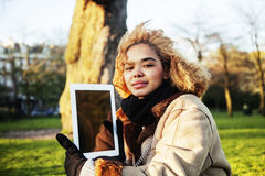 Young cute blond african american girl student holding tablet an Stock Photography