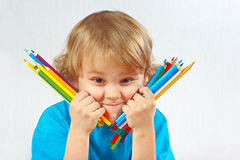 Young cute blond boy holds color pencils Royalty Free Stock Photos