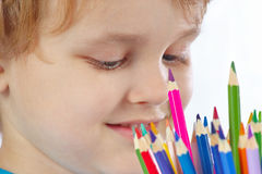 Young cute blond boy looks on color pencils Stock Photography