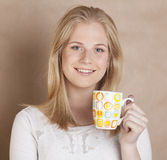 Young cute blond girl drinking coffee close up on Stock Photography