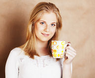 Young cute blond girl drinking coffee close up on warm brown bac Stock Images