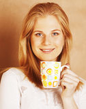 Young cute blond girl drinking coffee close up on warm brown bac Stock Photos