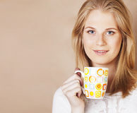 Young cute blond girl drinking coffee close up on warm brown bac Royalty Free Stock Images