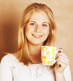 Young cute blond girl drinking coffee close up on warm brown bac Stock Image