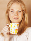 Young cute blond girl drinking coffee close up on warm brown background Stock Image