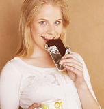 Young cute blond girl eating chocolate and Royalty Free Stock Image