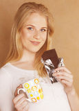 Young cute blond girl eating chocolate and drinking coffee close up Stock Photo