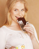 Young cute blond girl eating chocolate and drinking coffee close up Royalty Free Stock Images