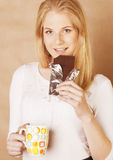 Young cute blond girl eating chocolate and drinking coffee close up Royalty Free Stock Photos