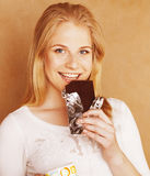 Young cute blond girl eating chocolate and drinking coffee close Royalty Free Stock Photo