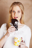 Young cute blond girl eating chocolate and drinking coffee close Royalty Free Stock Images
